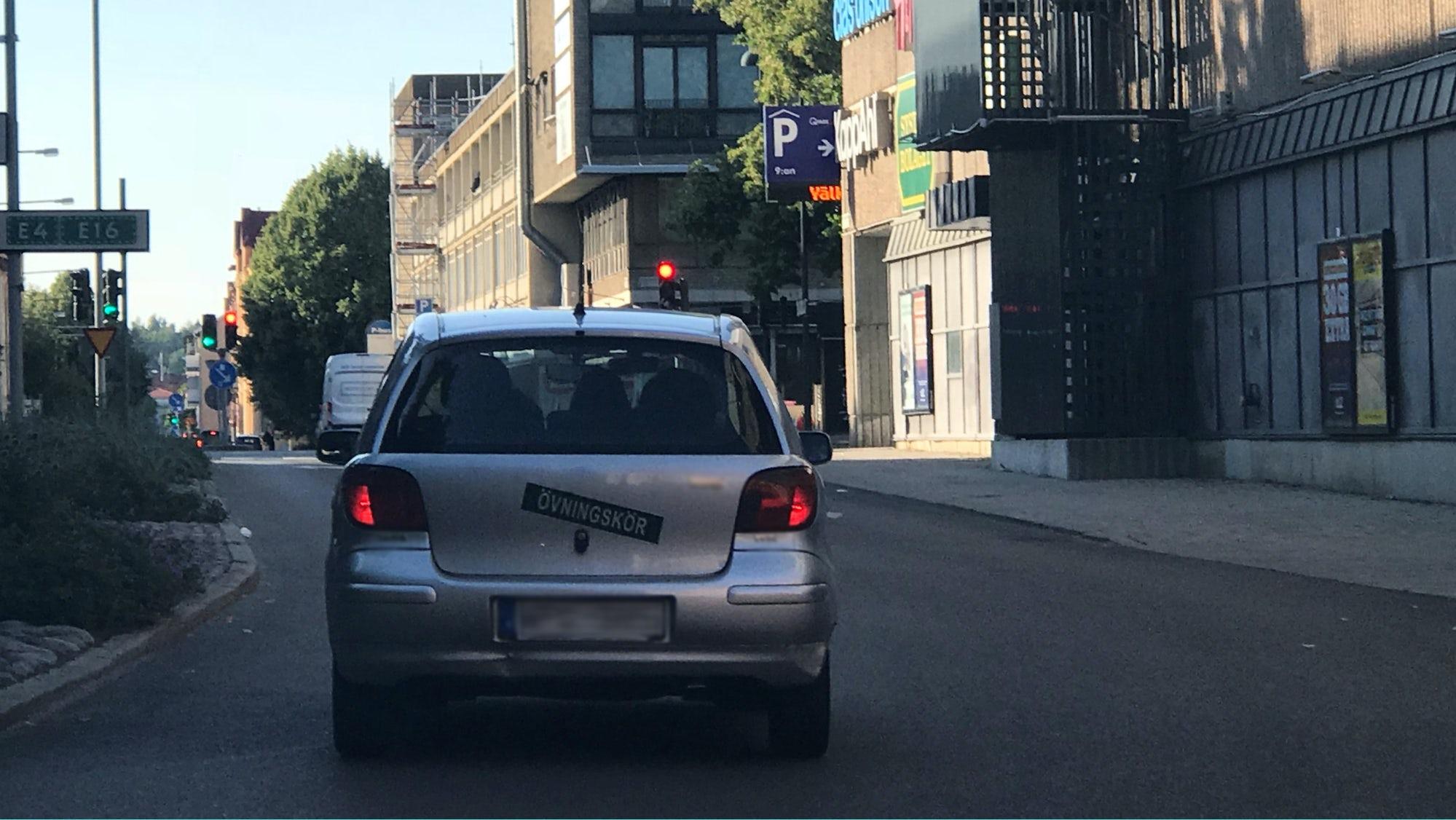 Bil som har övningskörningsskylt uppsatt på bakluckan.