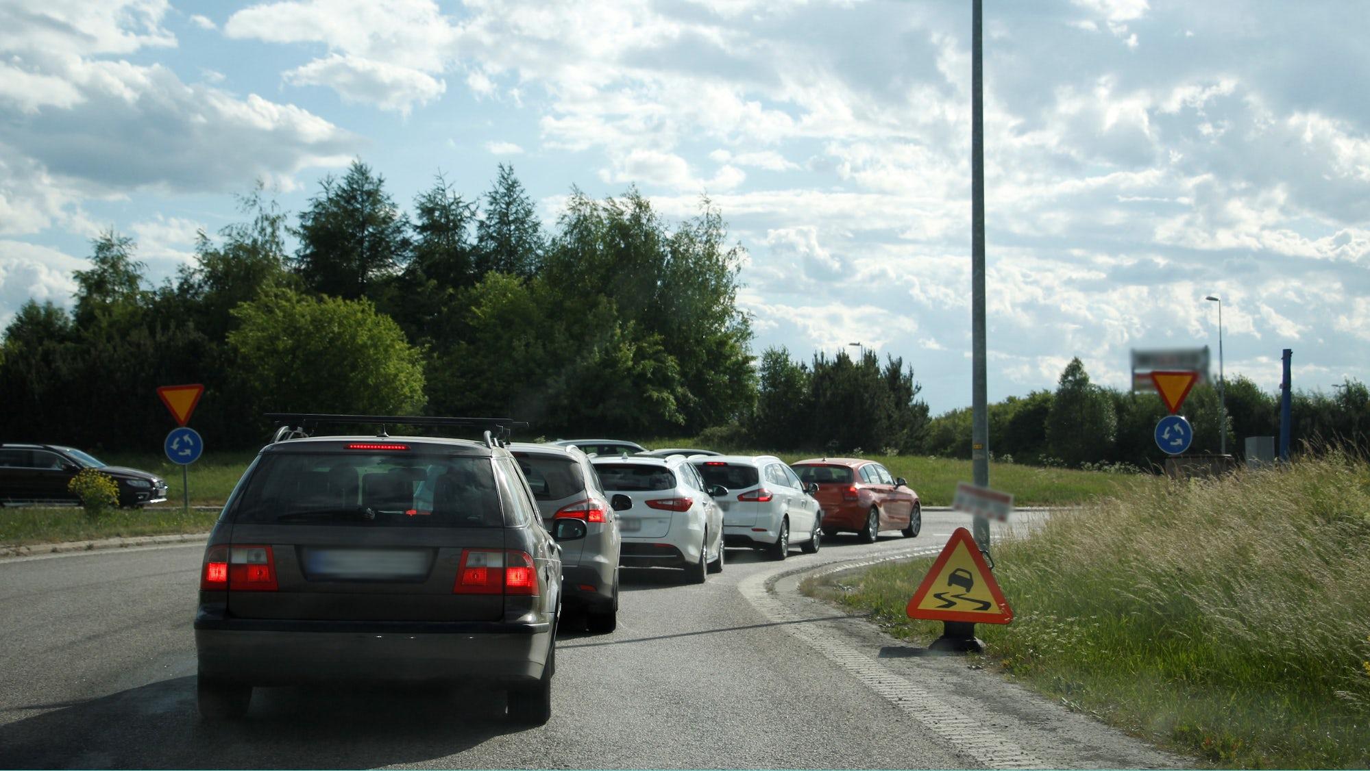 Flera bilar som väntar på att få köra in i en cirkulationsplats.