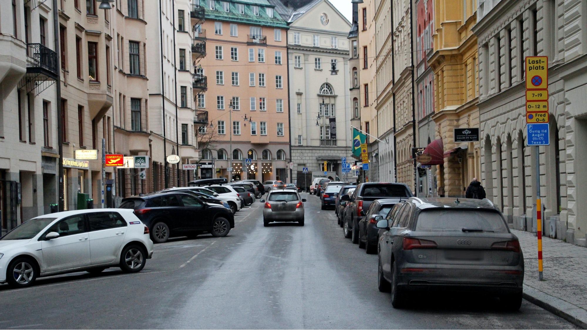 Bil på trång gata där det är många parkerade bilar.