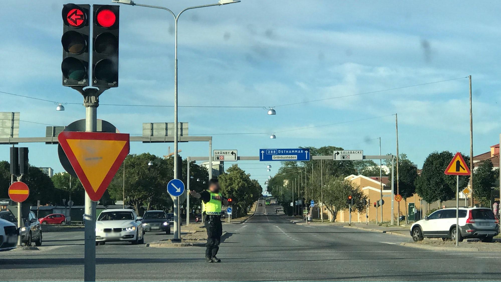 Polis som står och dirigerar trafik i en trafikerad korsning.