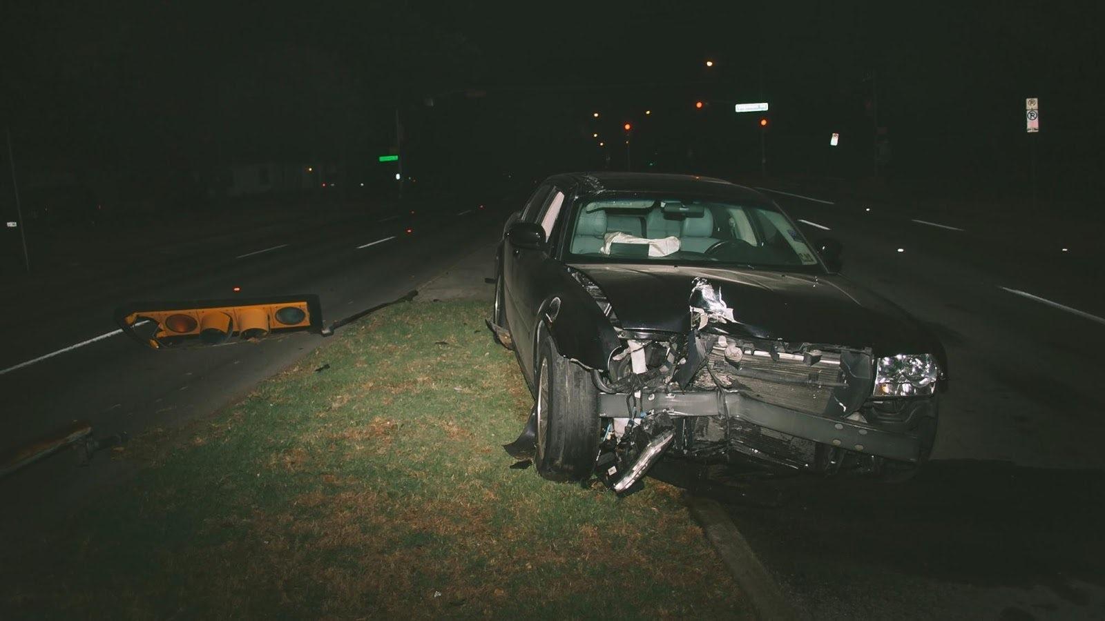 En krockad bil som står på mittremsan mellan två vägar.