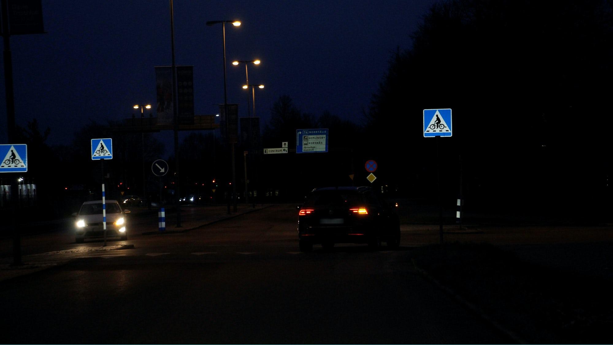 Bil som svänger vänster i en korsning när det är mörkt ute.