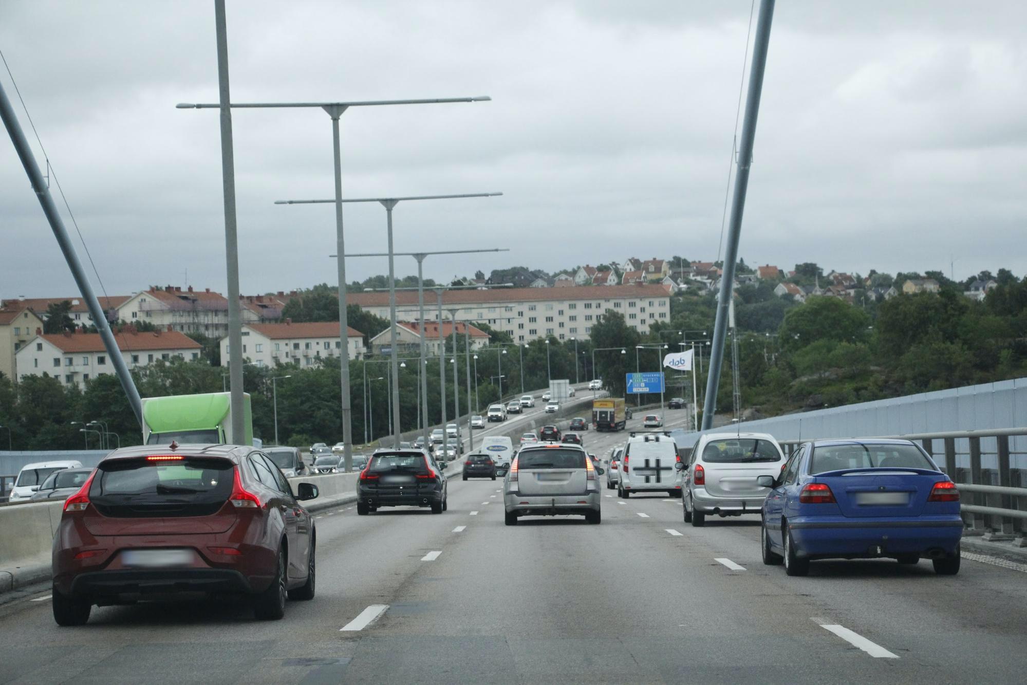 Bilar som kör på en bro på en trefilig väg.