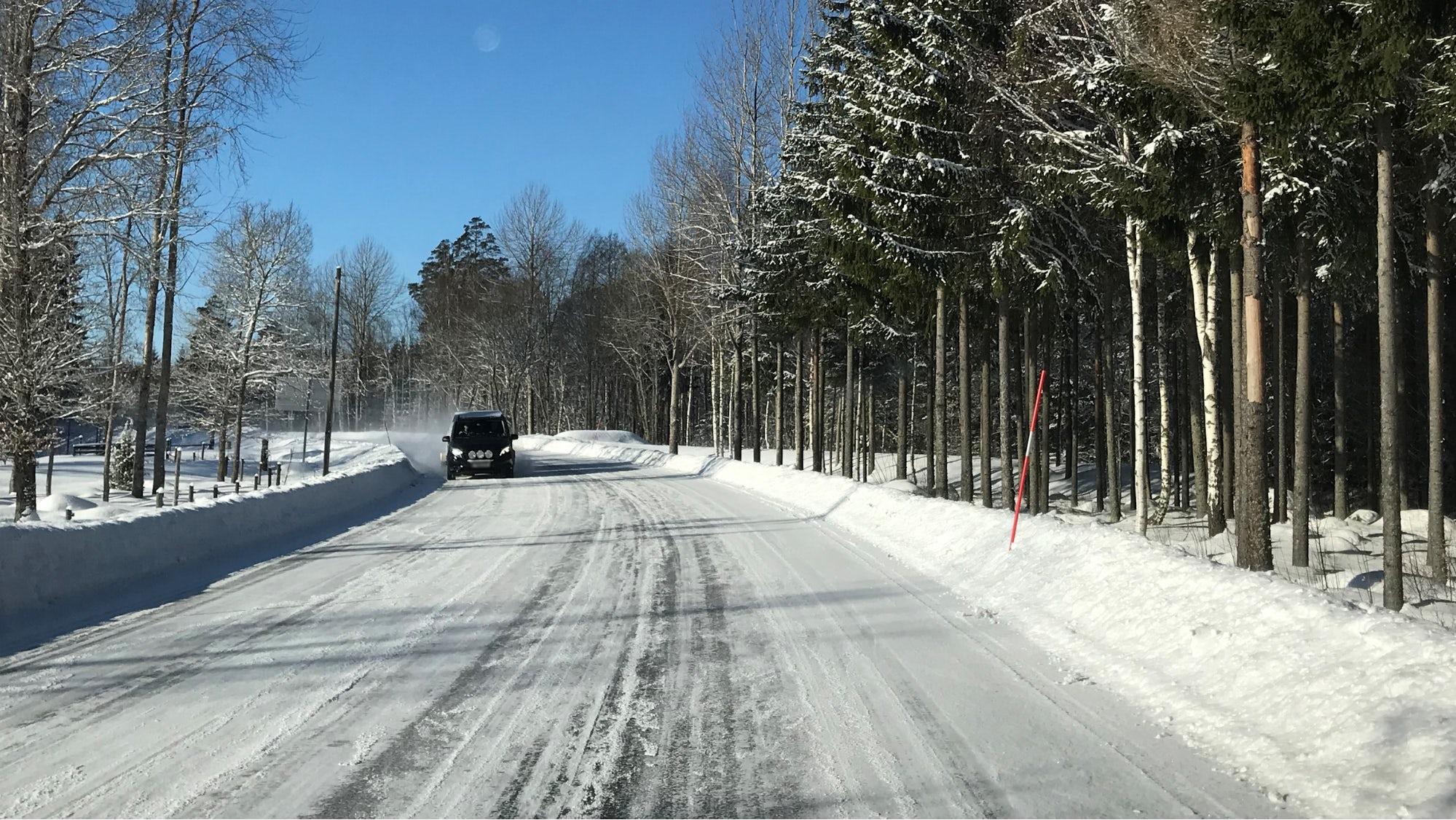 Mötande bil vid körning när det är vinterväglag.