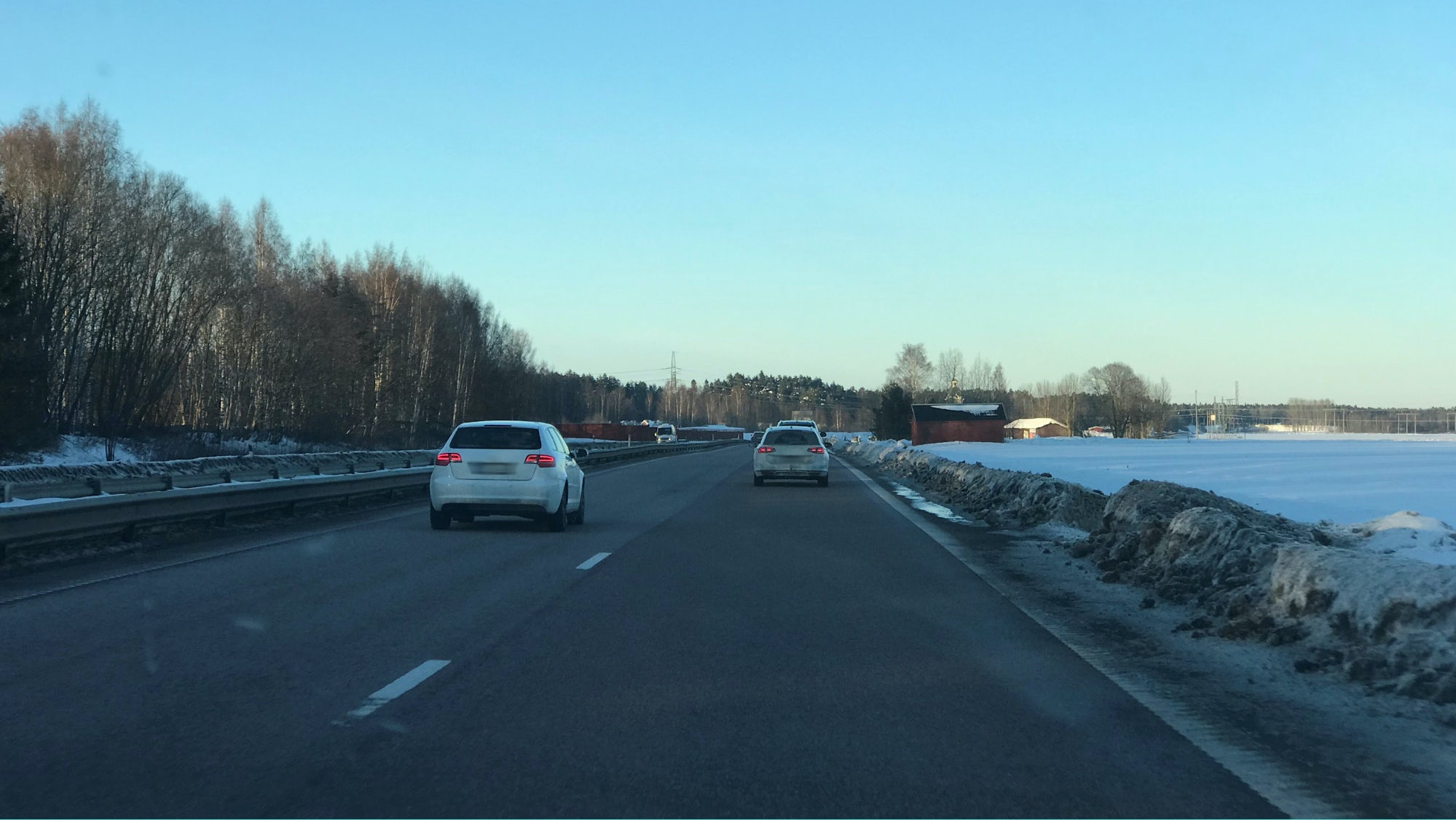 Motorväg där det är två bilar körandes. En i vänster fil och en i höger fil.